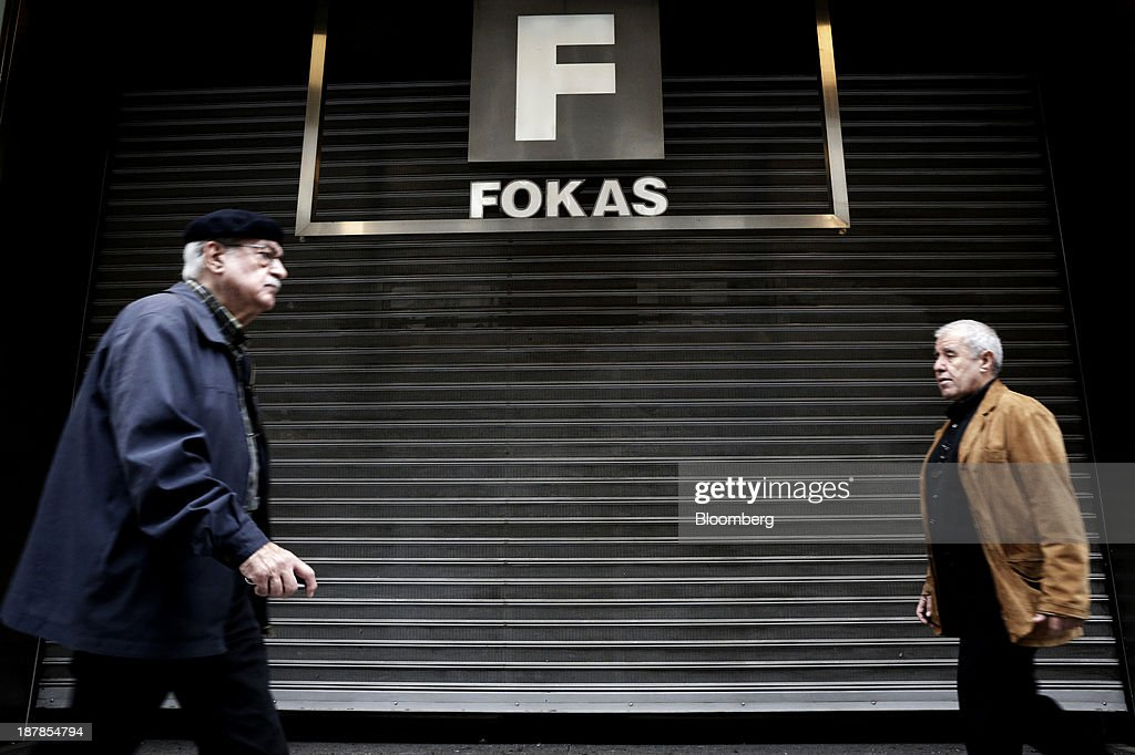Pedestrians pass the shutters of a closed down department store in Thessaloniki, Greece, on Wednesday, Nov. 13, 2013. Greece 'is following a fiscal adjustment program that aims to make the country's public finances sustainable on a permanent basis,' Finance Minister Yannis Stournaras told lawmakers during the debate, after holding talks with the troika earlier in the week. Photographer: Konstantinos Tsakalidis/Bloomberg via Getty Images
