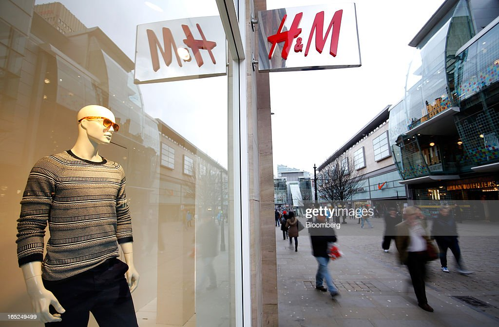 Pedestrians pass the window display of a Hennes & Mauritz AB (H&M) fashion store in Manchester, U.K., on Monday, April 1, 2013. U.K. retail sales unexpectedly stagnated in March in a sign that consumer spending remains under pressure from higher energy bills and weak wage growth. Photographer: Paul Thomas/Bloomberg via Getty Images
