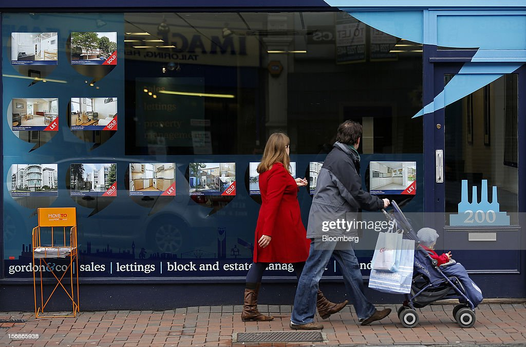 Pedestrians pass the window display of an estate agents in the Clapham district of London, U.K., on Friday, Nov. 23, 2012. U.K. mortgage approvals rose to a nine-month high in October, the British Bankers' Association said. Photographer: Simon Dawson/Bloomberg via Getty Images