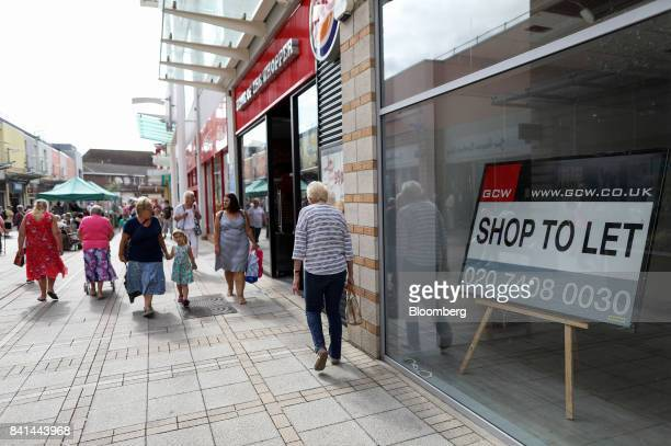 Pedestrians pass the window of a empty retail store containing a 'Shop to Let' sign in the Vancouver Quarter openair mall in King's Lynn UK on...