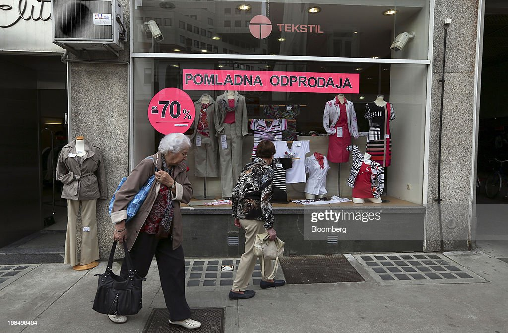Pedestrians pass the window of a fashion store advertising price discounts in Ljubljana, Slovenia, on Friday, May 10, 2013. The Adriatic nation is seeking to fix its ailing lenders with a cash injection of at least 900 million euros ($1.17 billion) after Cyprus's bailout focused investors on countries with weak banking industries. Photographer: Chris Ratcliffe/Bloomberg via Getty Images