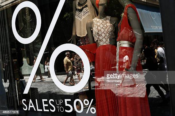 Pedestrians pass the window of a fashion store advertising sales discounts in the summer sales in Athens Greece on Monday July 13 2015 Greece has...
