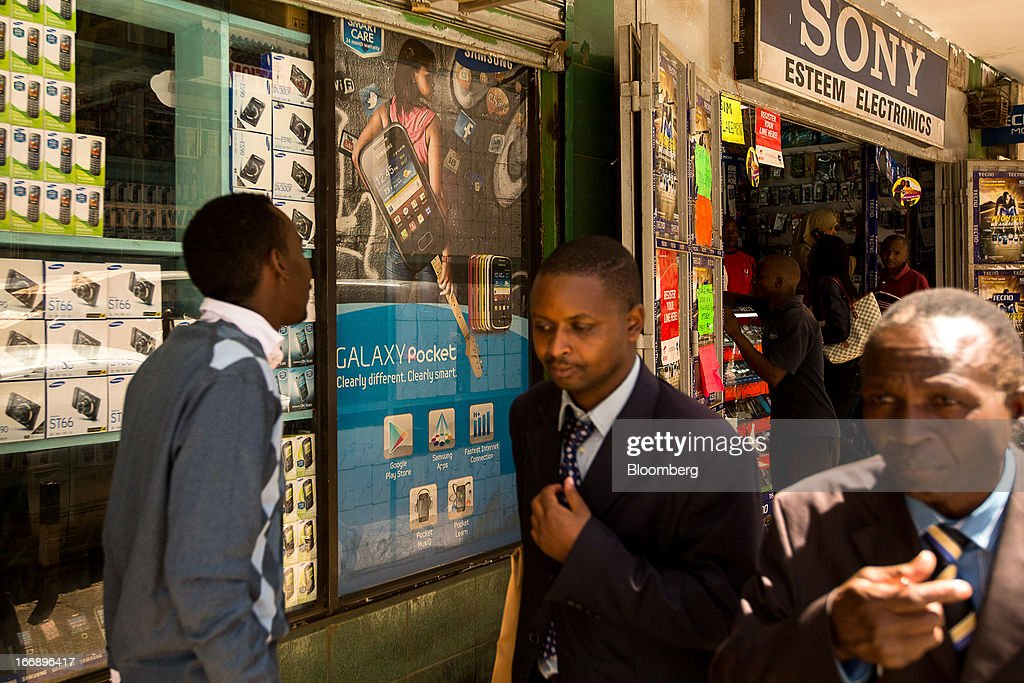 Pedestrians pass the window of a mobile phone store specialising in the sale of Samsung Electronics Co. handsets in Nairobi, Kenya, on Wednesday, April 17, 2013. Though only 23 percent of houses there have electricity and just 9 percent of roads are paved, mobile-phone penetration is 75 percent in the country, up from 5 percent in 2003. Photographer: Trevor Snapp/Bloomberg via Getty Images