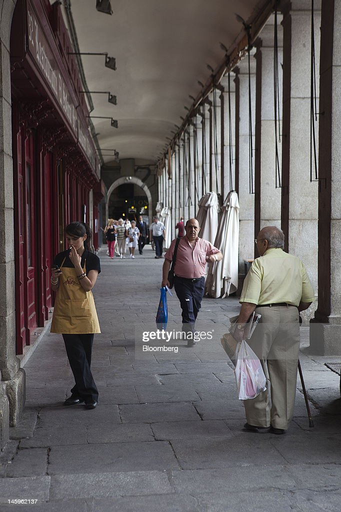Pedestrians pass through a colonnaded arcade in Madrid, Spain, on Friday, June 8, 2012. Spain is poised to become the fourth of the 17 euro-area countries to require emergency assistance as the currency bloc's finance chiefs plan weekend talks on a potential aid request to shore up the nation's lenders. Photographer: Angel Navarrete/Bloomberg via Getty Images