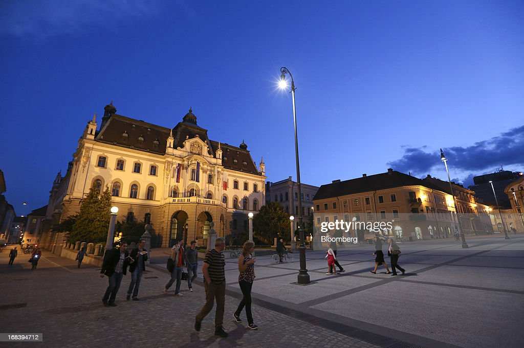 Pedestrians pass University of Ljubljana buildings, left, illuminated by evening light in Ljubljana, Slovenia, on Wednesday, May 8, 2013. Slovenia's recession will stretch into next year on weak domestic demand as the euro-area country teeters on the brink of needing an international bailout, the European Commission said. Photographer: Chris Ratcliffe/Bloomberg via Getty Images