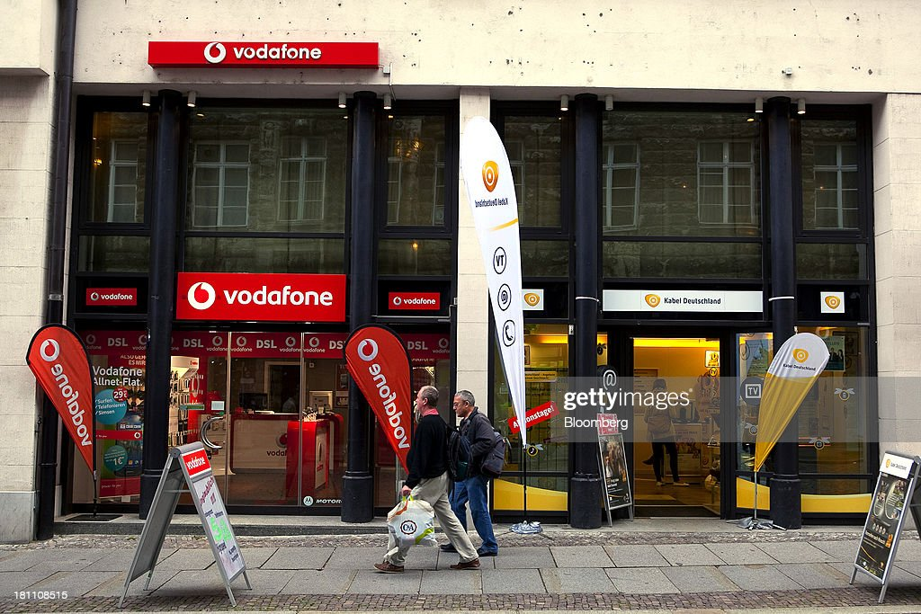 Pedestrians pass Vodafone Group Plc, left, and Kabel Deutschland Holding AG stores as they sit side by side in Leipzig, Germany, on Wednesday, Sept. 18, 2013. Vodafone Group Plc's 7.7 billion-euro ($10.2 billion) bid for Kabel Deutschland Holding AG cleared a major hurdle by winning the backing of at least 75 percent of the German company's shareholders. Photographer: Krisztian Bocsi/Bloomberg via Getty Images