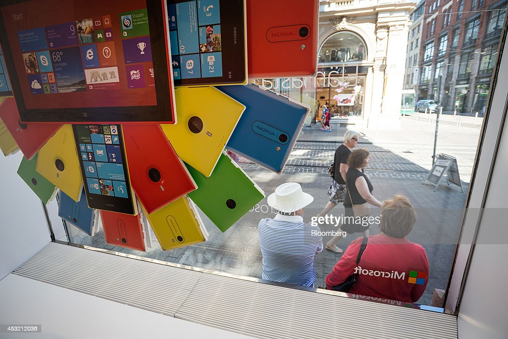 Pedestrians pause outside a window display for Nokia Lumia mobile devices in window of the flagship Nokia Oyj mobile phone store in central Helsinki...