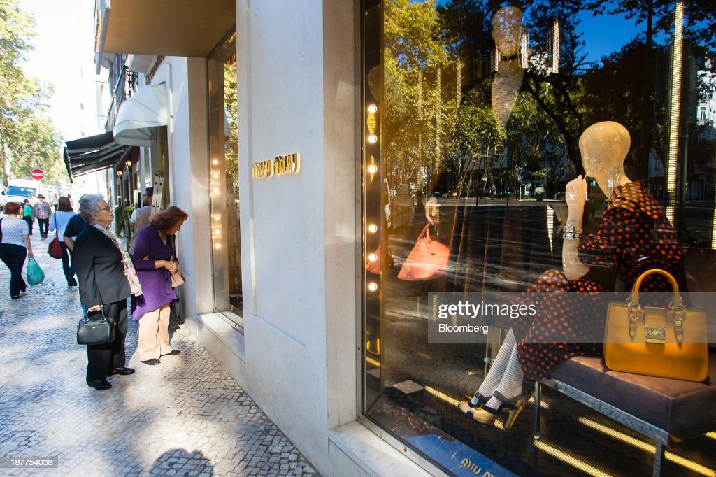 Pedestrians pause to browse the window display of a Miu Miu luxury fashion store, operated by Prada SpA, in Lisbon, Portugal, on Tuesday, Nov. 12, 2013. Portugal's jobless rate dropped for a second quarter, falling to 15.6 percent in the three months through September as the country's economy shows signs of recovery. Mario Proenca/Bloomberg via Getty Images
