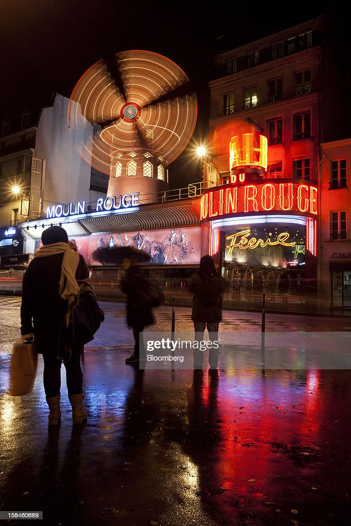 Pedestrians photograph the illuminated windmill at the Moulin Rouge cabaret house in Paris, France, on Saturday, Dec. 15, 2012. The French minister for energy and environment unveiled a proposal for lights in and outside shops, offices, and public buildings -- including the flagship Louis Vuitton store and the Lido cabaret house on Paris's Avenue des Champs Elysees -- to be turned off between 1 a.m. and 7 a.m. starting in July. Photographer: Balint Porneczi/Bloomberg via Getty Images