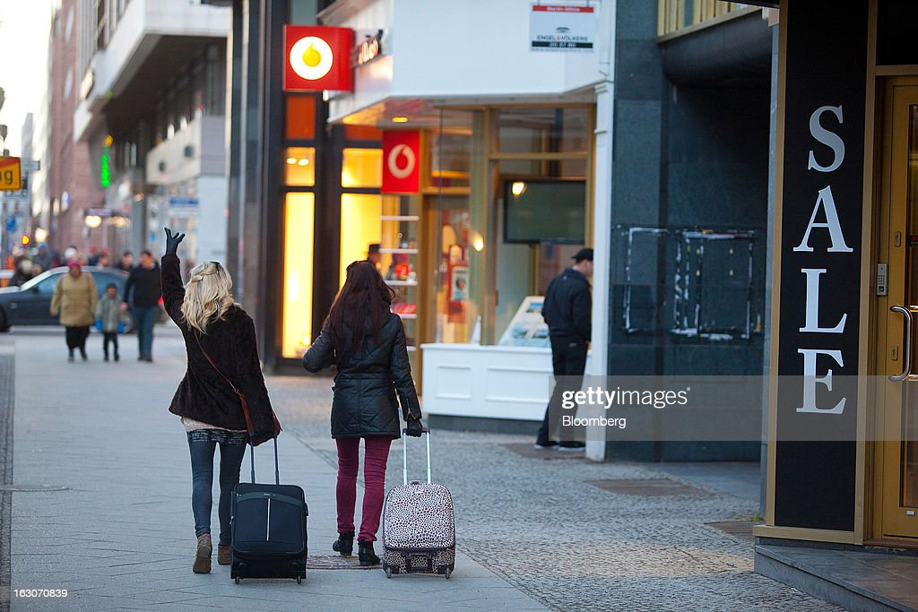 Pedestrians pull suitcases past a sale sign outside a retail store on Friedrichstrasse in the Mitte district of Berlin, Germany, on Sunday, March 3, 2013. Germany's 10-year government bonds advanced for a second day even before a report that economists said will show producer prices in the euro area increased for the first time in four months in January. Photographer: Krisztian Bocsi/Bloomberg via Getty Images