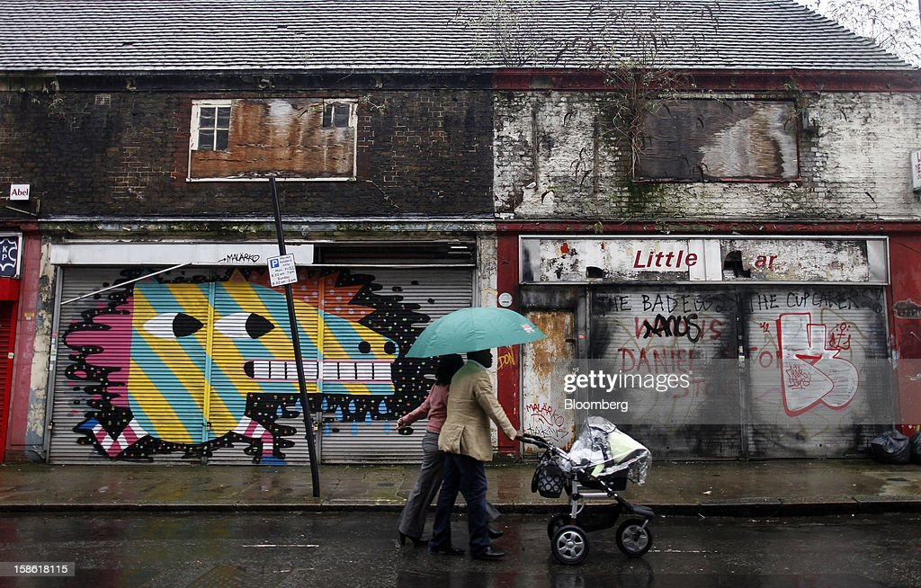 Pedestrians push a baby buggy past closed-down retail stores in London, U.K., on Thursday, Dec. 20, 2012. Britain's economy expanded less than previously estimated in the third quarter and the budget deficit unexpectedly widened in November, complicating Prime Minister David Cameron's attempts to bolster the recovery. Photographer: Simon Dawson/Bloomberg via Getty Images