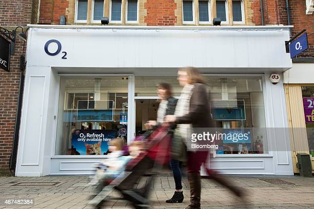 Pedestrians push baby strollers past the entrance to an O2 mobile phone store operated by Telefonica SA in Horsham UK on Wednesday March 25 2015 Li...