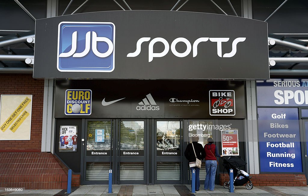 Pedestrians read a notice posted in the window of a closed down JJB store in Stockport, U.K., on Saturday, Oct. 6, 2012. JJB Sports Plc, a U.K. sporting goods retailer, will close most of its stores with the remaining 20 being acquired by competitor Sports Direct International Plc, according to a statement from KPMG LLP, which was appointed as administrator to the Wigan, England-based company. Photographer: Paul Thomas/Bloomberg via Getty Images
