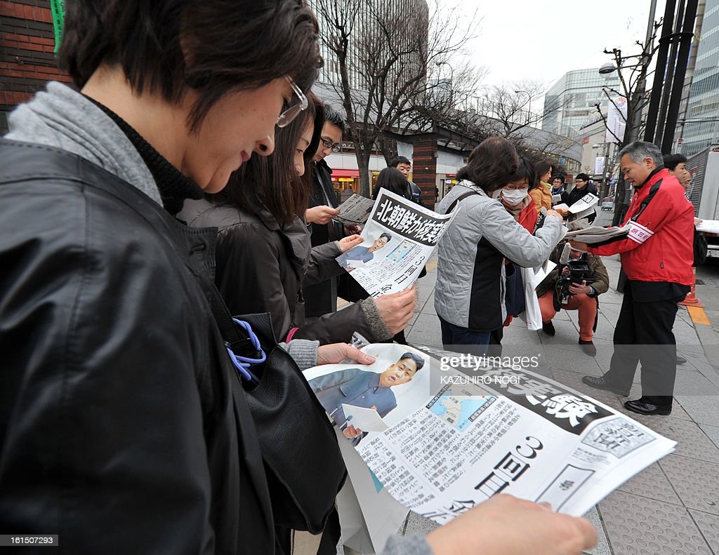 Pedestrians read extra edition newspapers to pedestrians reporting on North Korea's nuclear test, in downtown Tokyo on February 12, 2013. North Korea's nuclear test is a 'grave threat' to Japan, Prime Minister Shinzo Abe said on February 12, hours after Pyongyang confirmed it had successfully detonated an atomic device.