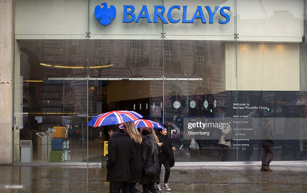 Pedestrians shelter from rain and sleet beneath Union Jack flag umbrellas as they pass a Barclays Plc bank branch in London, U.K., on Monday, Feb. 11, 2013. Barclays Plc Chief Executive Officer Antony Jenkins's pledges to shred the legacy of his predecessor and fix the lender's culture are distracting from the difficulty he has in reviving profit at Britain's biggest investment bank. Photographer: Simon Dawson/Bloomberg via Getty Images