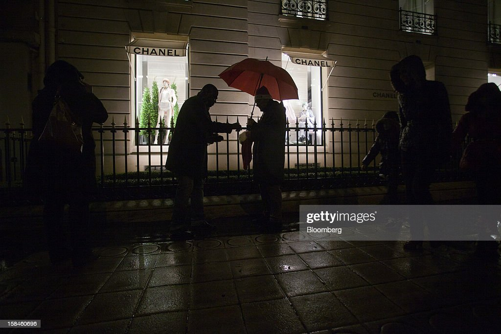 Pedestrians shelter from the rain beneath an umbrella outside the illuminated window display of a Chanel store, in Paris, France, on Saturday, Dec. 15, 2012. The French minister for energy and environment unveiled a proposal for lights in and outside shops, offices, and public buildings -- including the flagship Louis Vuitton store and the Lido cabaret house on Paris's Avenue des Champs Elysees -- to be turned off between 1 a.m. and 7 a.m. starting in July. Photographer: Balint Porneczi/Bloomberg via Getty Images