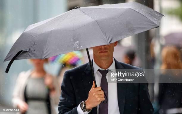 Pedestrians shelter from the rain beneath umbrellas as rain falls in central London on August 9 2017 / AFP PHOTO / Tolga Akmen
