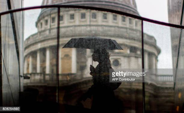Pedestrians shelter from the rain beneath umbrellas as rain falls near St Paul's Cathedral in central London on August 9 2017 / AFP PHOTO / Tolga...