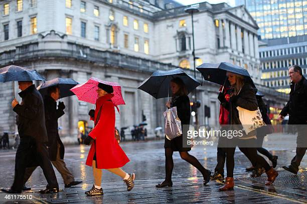 Pedestrians shelter from the rain beneath umbrellas as they cross a road opposite the Bank of England in London UK on Thursday Jan 8 2015 The pound...