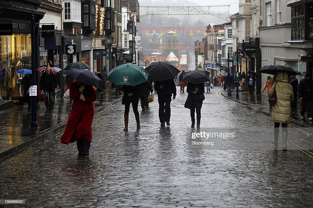 Pedestrians shelter from the rain beneath umbrellas as they walk along the cobbled high street in Guildford, U.K., on Friday, Dec. 14, 2012. Standard & Poor's lowered its outlook on Britain's top credit rating to negative, citing weak economic growth and a worsening debt profile. Photographer: Simon Dawson/Bloomberg via Getty Images