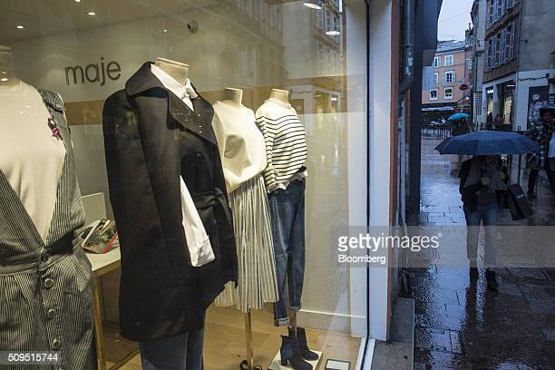 Pedestrians shelter under umbrellas as they pass a Maje luxury clothing store operated by SMCP Group in Toulouse France on Wednesday Feb 10 2016...