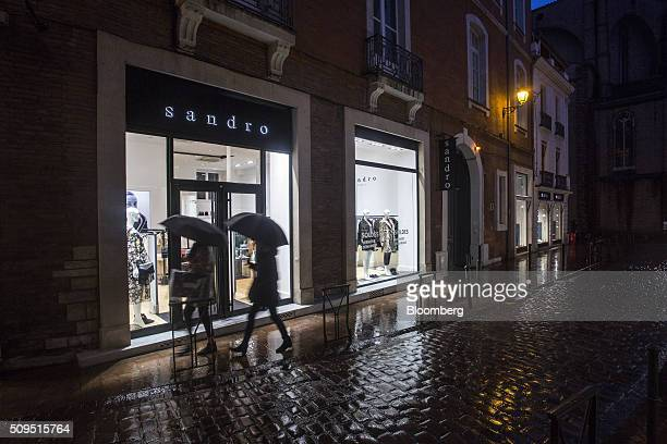 Pedestrians shelter under umbrellas as they pass a Sandro luxury clothing store operated by SMCP Group at night in Toulouse France on Wednesday Feb...