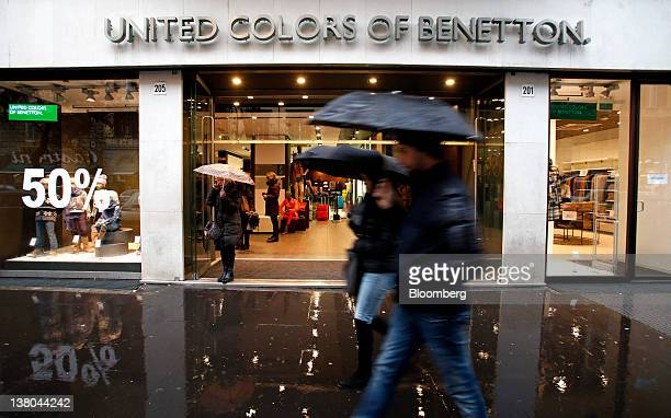 Pedestrians shelter under umbrellas as they pass a United Colors of Benetton store operated by Benetton Group SpA in Rome Italy on Wednesday Feb 1...