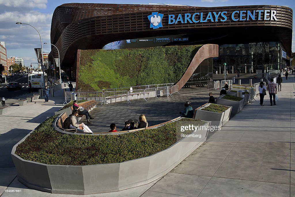 Pedestrians sit on front of the Barclays Center in the Brooklyn borough of New York, U.S., on Sunday, Oct. 21, 2012. The Barclays Center, the 675,000-square-foot arena designed by SHoP Architects PC of Manhattan, opened on Sept. 28 with eight sold-out shows by rapper Jay-Z. Photographer: Victor J. Blue/Bloomberg via Getty Images