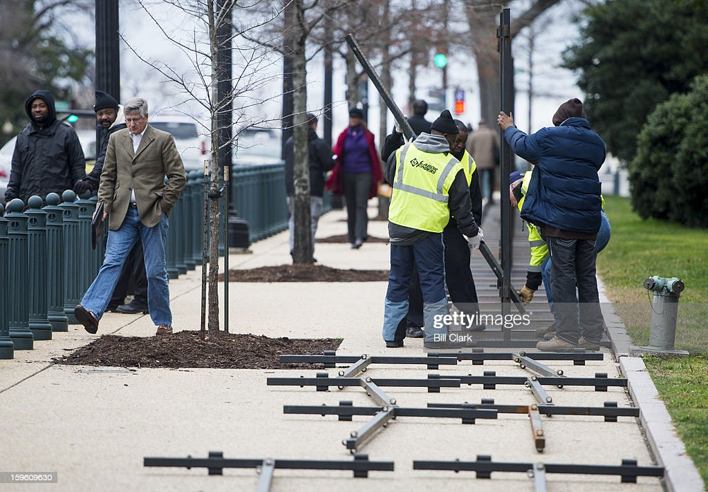 Pedestrians skirt past workers as they set up security fencing in front of the Rayburn House Office Building on Thursday, Jan. 17, 2013, in preparation for President Barack Obama's inauguration.