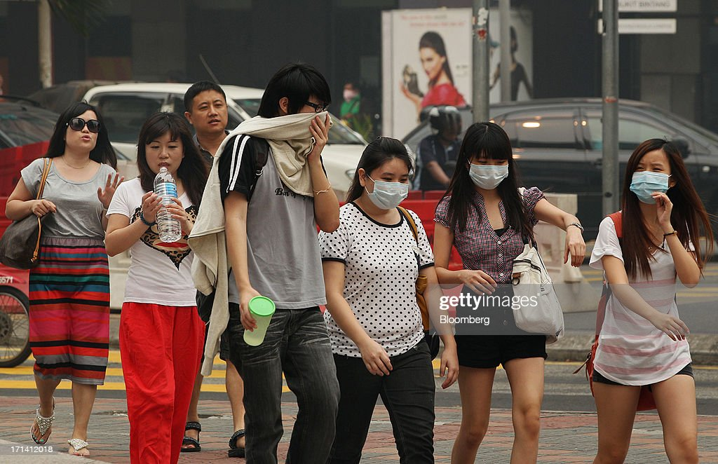 Pedestrians, some wearing face masks, cross a street in Kuala Lumpur, Malaysia, on Monday, June 24, 2013. Malaysia called for a meeting of Southeast Asian ministers as early as next week after haze from illegal Indonesian forest fires reached hazardous levels in parts of the region. Photographer: Goh Seng Chong/Bloomberg via Getty Images