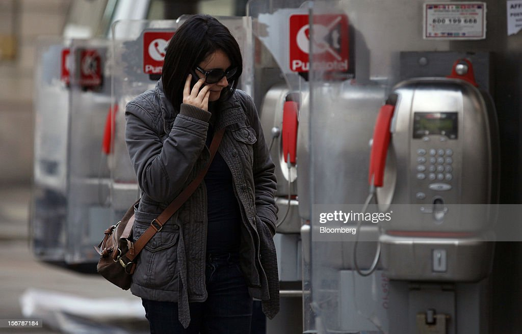 A pedestrians speaks on a mobile phone as she passes public payphones operated by Telecom Italia SpA, in Milan, Italy, on Tuesday, Nov. 20, 2012. Telecom Italia SpA said it is still reviewing the possible spinoff of its fixed-line network and the company's board will discuss the outcome of its analysis on Dec. 6. Photographer: Alessia Pierdomenico/Bloomberg via Getty Images