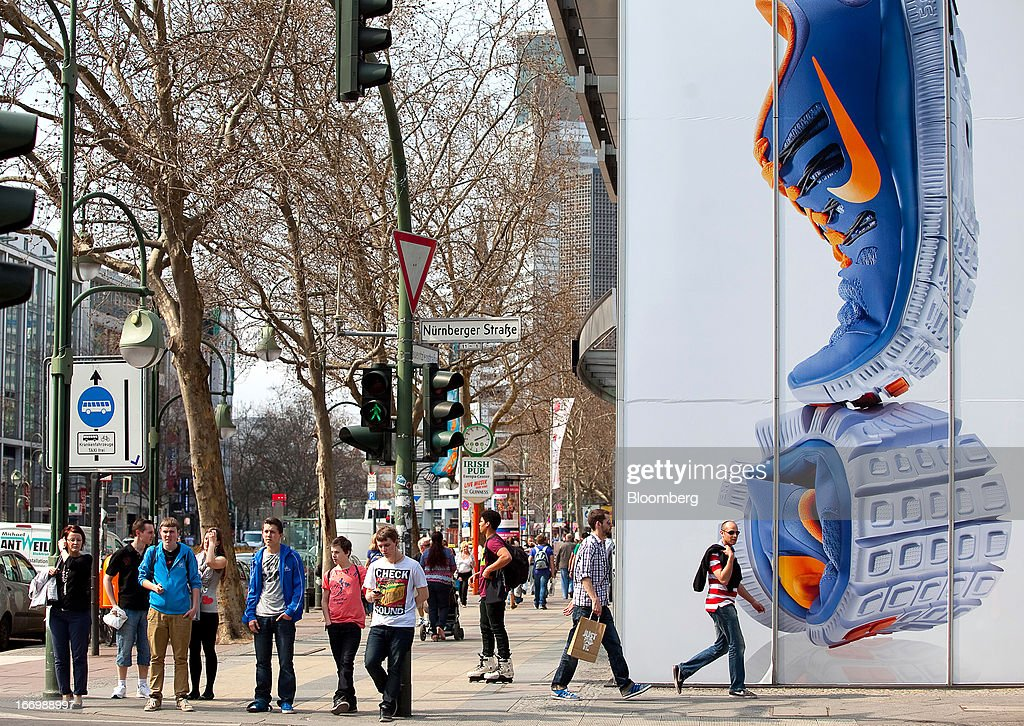 Pedestrians stand at a traffic crossing alongside a giant poster for Nike Inc. trainers in Berlin, Germany, on Thursday, April 18, 2013. Germany's economy is shrugging off a contraction at the end of last year and starting to grow due to revived exports and rising private consumption, the country's leading economic institutes said. Photographer: Krisztian Bocsi/Bloomberg via Getty Images