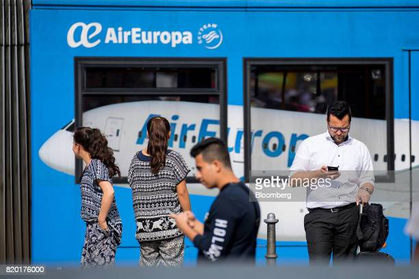 Pedestrians stand in front of a bus decorated with AirEuropa advertising in Frankfurt Germany on Thursday July 20 2017 Frankfurt has emerged as a...
