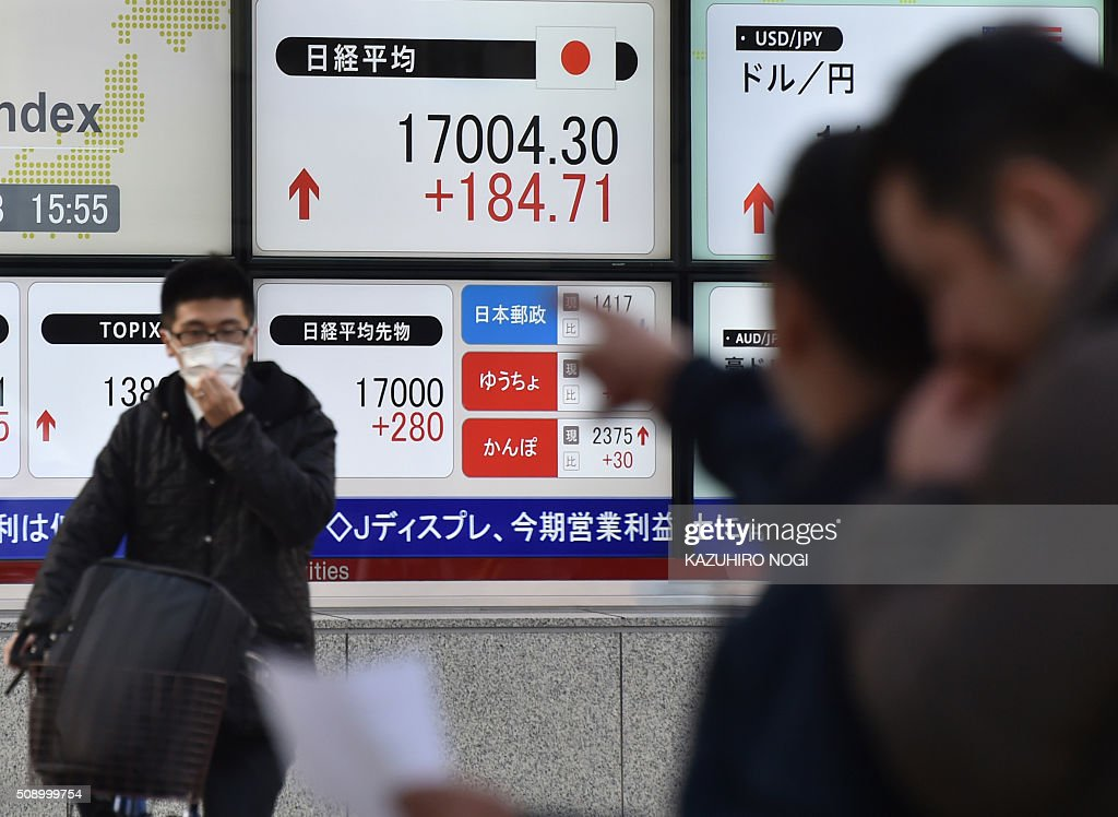 Pedestrians stand in front of a share prices board (top C) showing numbers of the Tokyo Stock Exchange in Tokyo on February 8, 2016. Tokyo stocks cast off early losses to finish higher February 8, buoyed by a weaker yen and upbeat economic data. AFP PHOTO / KAZUHIRO NOGI / AFP / KAZUHIRO NOGI
