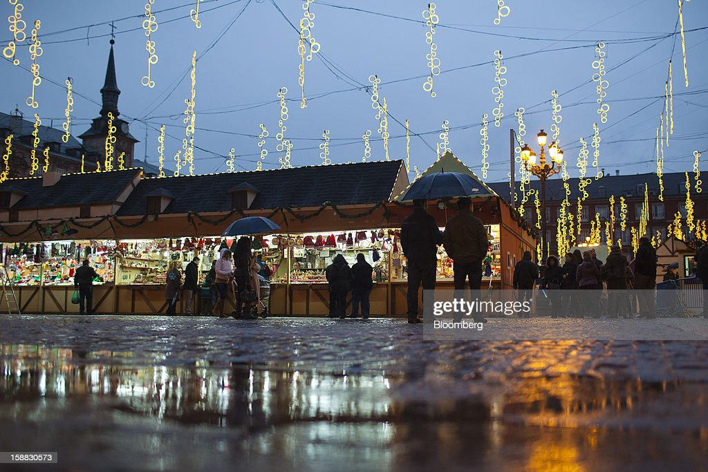 Pedestrians stand in front of kiosks in the rain at a Christmas market in Madrid, Spain, on Saturday, Dec. 29, 2012. Spain's economic activity kept falling in the fourth quarter, Bank of Spain says. Photographer: Angel Navarrete/Bloomberg via Getty Images