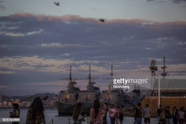 Pedestrians stand in front of navy ships docked outside a military facility in downtown Rio de Janeiro Brazil on Sunday July 30 2017 Thousands of...
