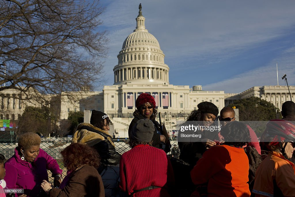 Pedestrians stand in front of the Capitol building ahead of the presidential inauguration in Washington, D.C., U.S., on Sunday, Jan. 20, 2013. As he enters his second term U.S. President Barack Obama has shed the aura of a hopeful consensus builder determined to break partisan gridlock and adopted a more confrontational stance with Republicans. Photographer: Victor J. Blue/Bloomberg via Getty Images