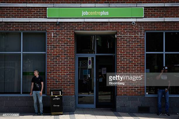 Pedestrians stand near the entrance to a job centre plus employment center in the Stratford district of London UK on Wednesday July 16 2014 UK...