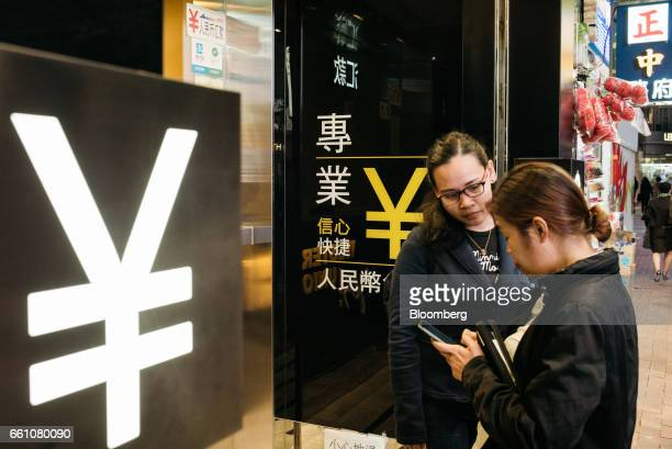 Pedestrians stand next to a sign for Japanese yen outside a currency exchange store in Hong Kong China on Thursday March 16 2017 Hong Kong's shopping...