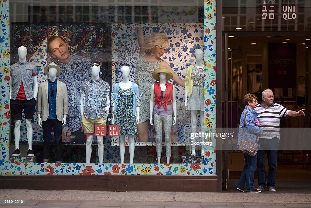 Pedestrians stand next to a window display outside a Uniqlo store, operated by Fast Retailing Co., on Regent Street in London, U.K., on Tuesday, May 24, 2016. U.K. retail sales began the second quarter with more momentum than economists forecast. Photographer: Simon Dawson/Bloomberg via Getty Images
