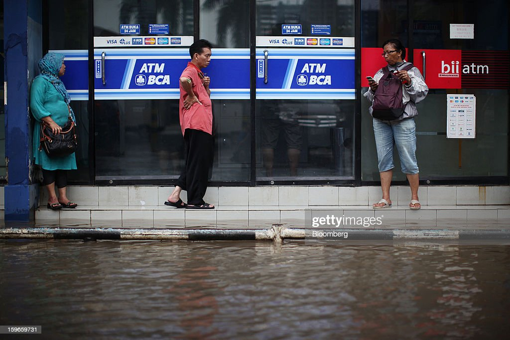 Pedestrians stand next to automated teller machine (ATM) facilities operated by PT Bank Central Asia (BCA) and PT Bank Internasional Indonesia (BII) as water floods a street in Jakarta, Indonesia, on Friday, Jan. 18, 2013. Indonesia declared a state of emergency in Jakarta as flooding brought traffic to a standstill in the city of 9.6 million people and swamped the offices of President Susilo Bambang Yudhoyono. Photograph by: Dimas Ardian/Bloomberg via Getty Images