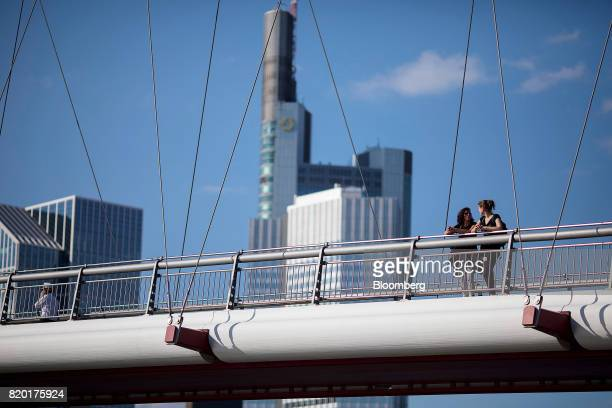 Pedestrians stand on a bridge spanning the River Maine as skyscrapers beyond in Frankfurt Germany on Thursday July 20 2017 Frankfurt has emerged as a...