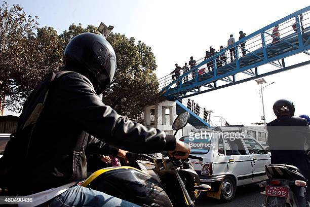 Pedestrians stand on a footbridge outside the Ratna Park bus station as traffic passes in Kathmandu Nepal on Wednesday Dec 3 2014 China this year...