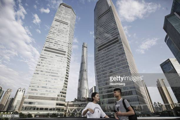 Pedestrians stand on an elevated walkway as the Shanghai Tower center stands in the background in the Lujiazui Financial District in Shanghai China...