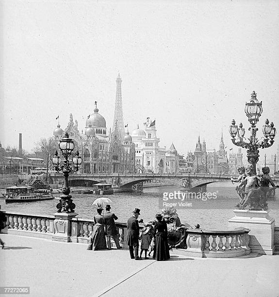 Pedestrians stand on the Alexandre III bridge at the Paris Exposition Universelle Paris France 1900 The Eiffel Tower is visible at center left