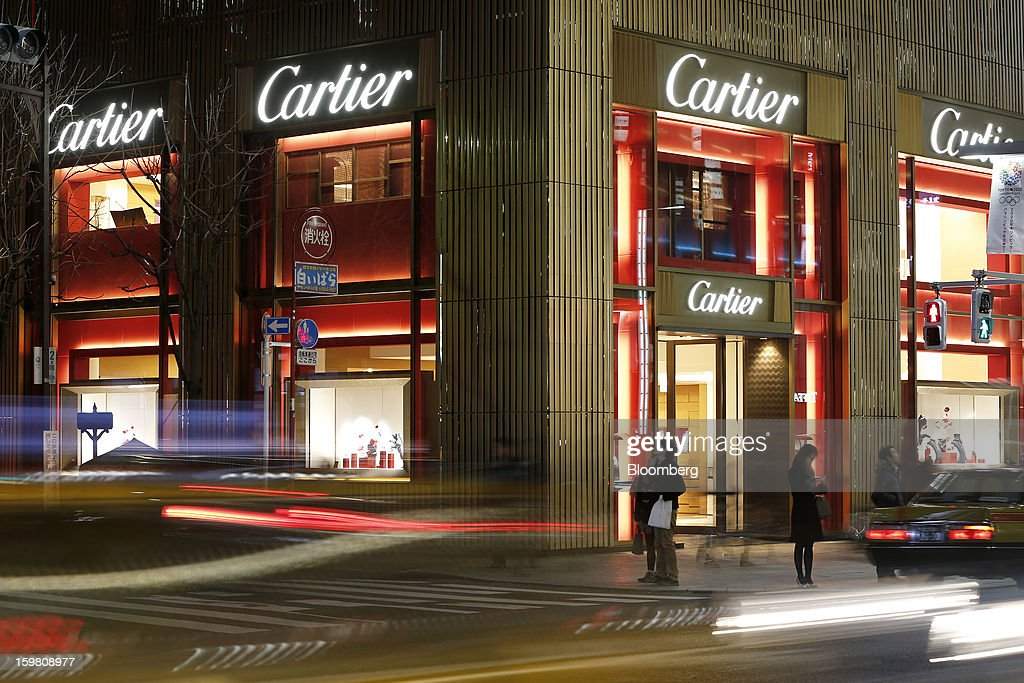 Pedestrians stand outside a Cie. Financiere Richemont SA's Cartier brand store, in this long exposure photograph taken in the Ginza district of Tokyo, Japan, on Sunday, Jan. 20, 2013. Japan's consumer prices excluding fresh food, a benchmark monitored by the central bank, haven't advanced 2 percent for any year since 1997, when a national sales tax was increased. Photographer: Kiyoshi Ota/Bloomberg via Getty Images
