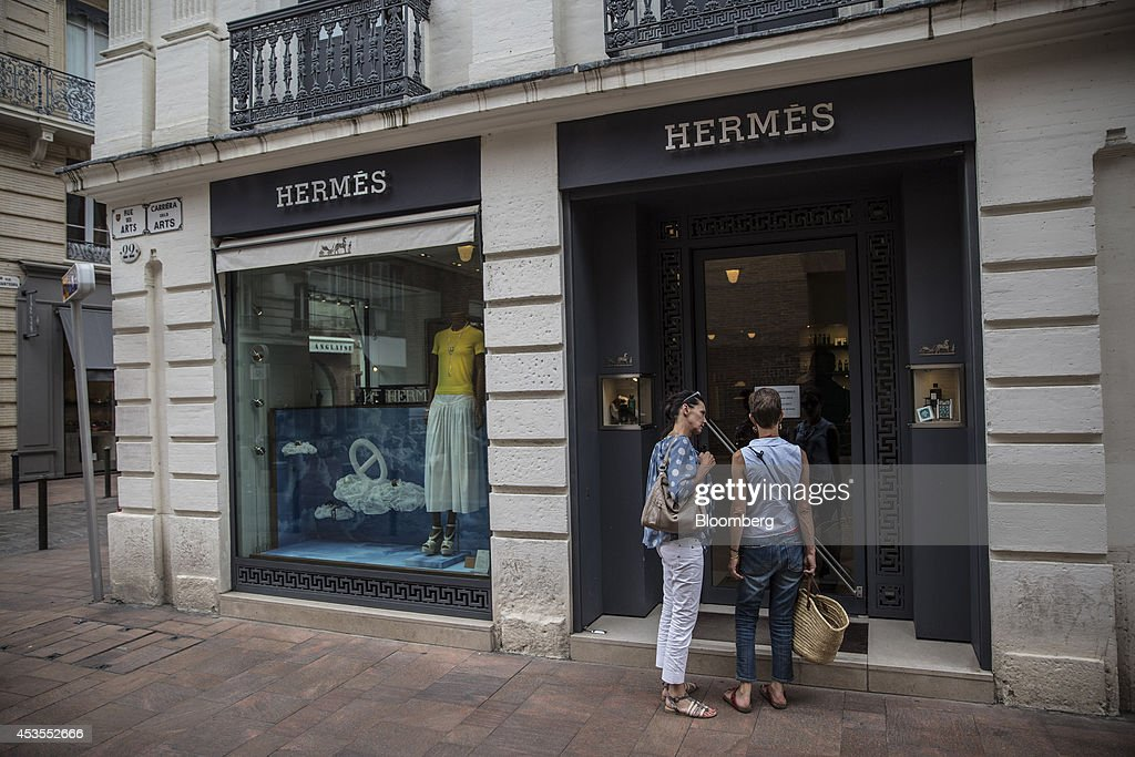Pedestrians stand outside a Hermes International SCA luxury goods store in Toulouse, France, on Tuesday, Aug. 12, 2014. The euro traded 0.3 percent from a nine-month low before reports this week that may show growth in the region weakened and inflation slowed, adding to signs the bloc's economy is struggling to recover. Photographer: Balint Porneczi/Bloomberg via Getty Images