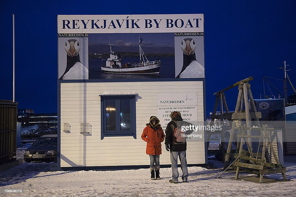 Pedestrians stand outside a hut advertising boat tours at the harbor in Reykjavik, Iceland, on Tuesday, Jan. 1, 2013. Iceland's inflation rate eased in December as central bank efforts to stabilize the krona with interest rate increases paid off. Photographer: Arnaldur Halldorsson/Bloomberg via Getty Images