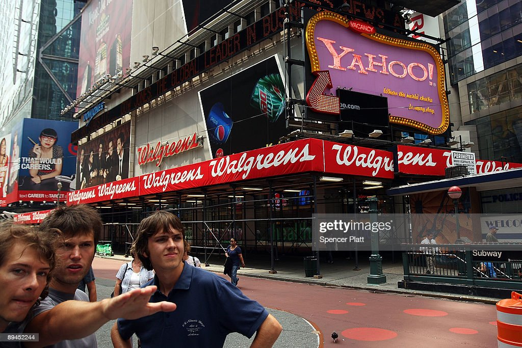 Pedestrians stop by a Yahoo sign in Times Square on July 29, 2009 in New York City. Taking aim at Google�s dominance, technology companies Microsoft and Yahoo announced Wednesday that they have reached a 10 year internet search partnership.
