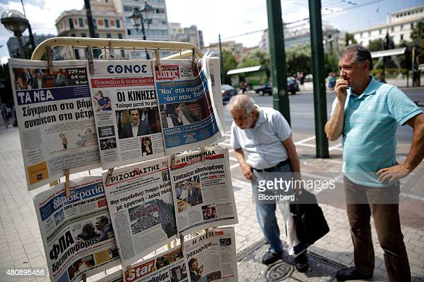Pedestrians stop to read the newspaper headlines outside a magazine kiosk in central Athens Greece on Thursday July 16 2015 While Greek lawmakers...